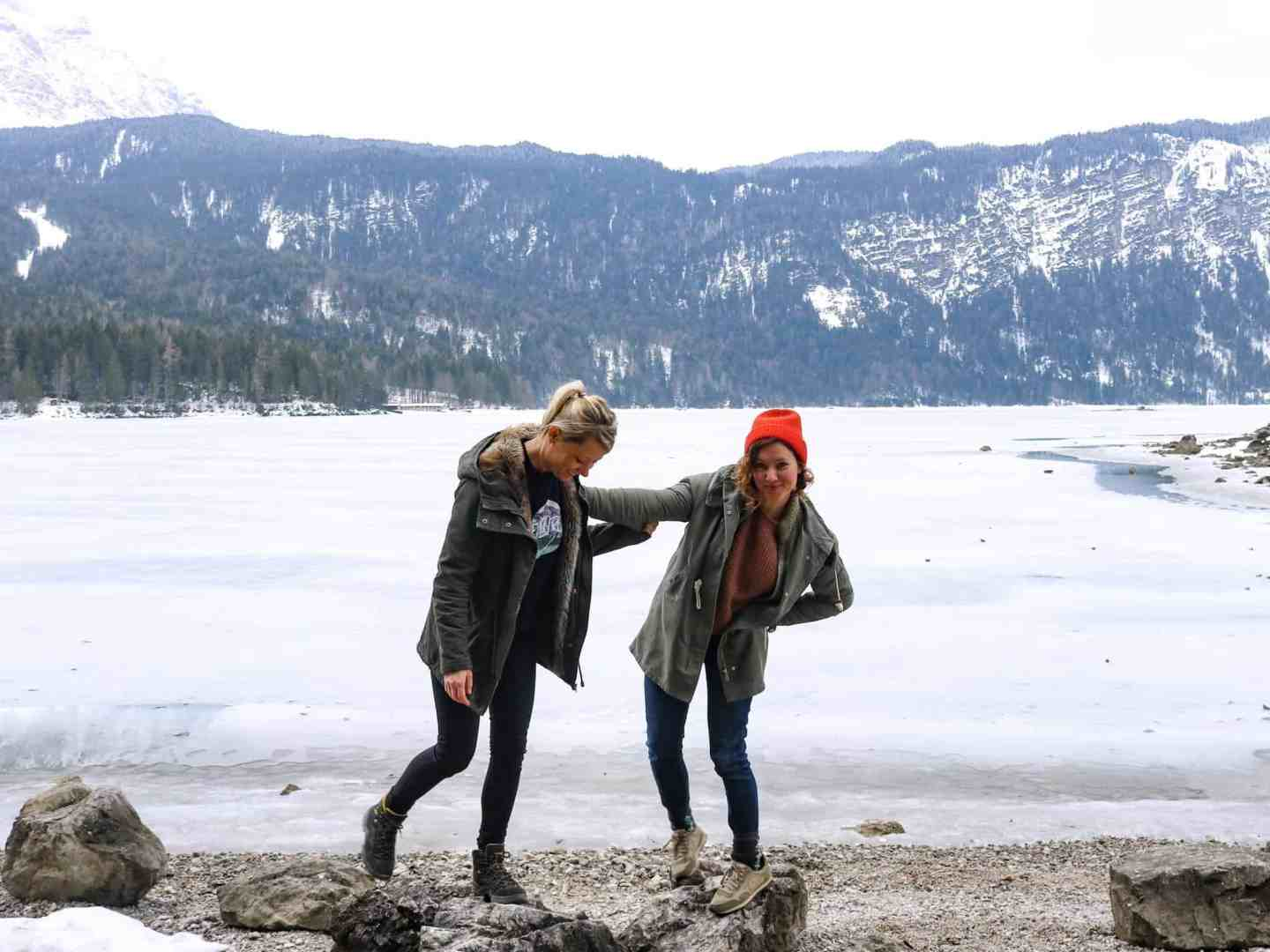 Two girls pushing eachother in front of a frozen lake