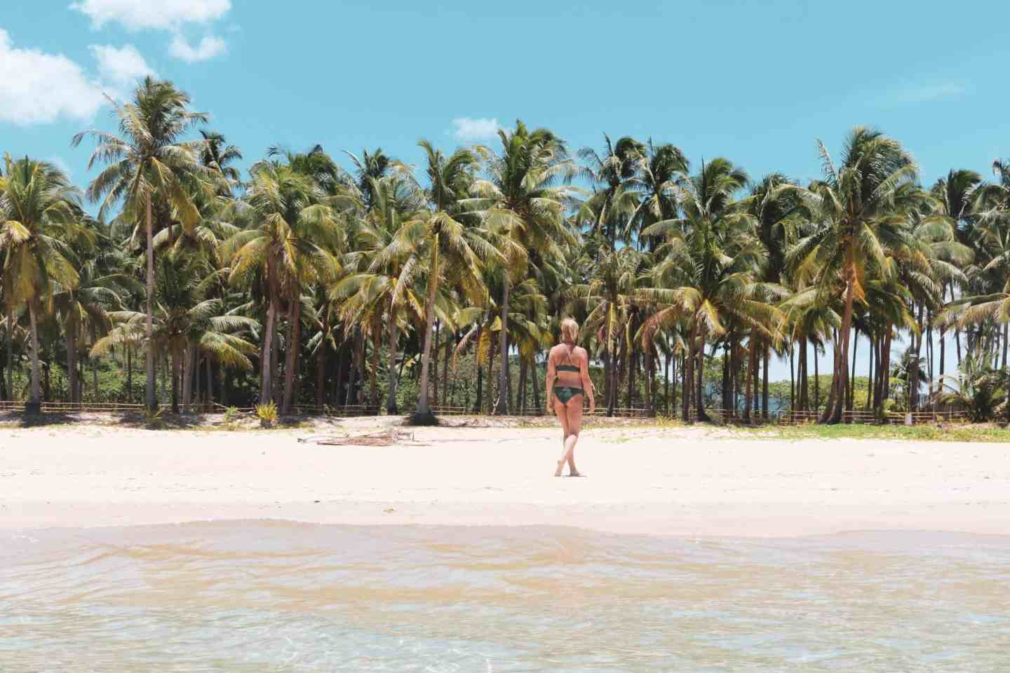 Girl on a Nacpan Beach full of palmtrees in El Nido