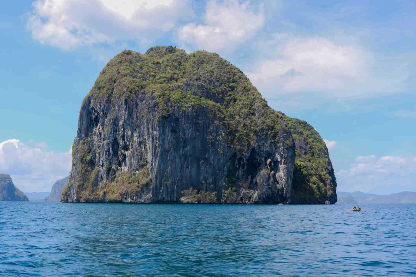 Islands with high cliffs in the middle of the ocean and a tiny canoe next to it in El Nido, Philippines