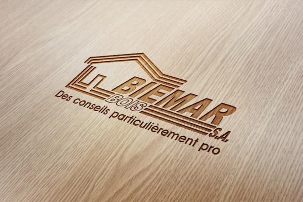 Biemar Bois - Des conseils particulièrement pro - Bois et Dérivés - Biemar - Caractère Advertising - Plan Média - Slogan - Mock Up logo sur fond bois gravé