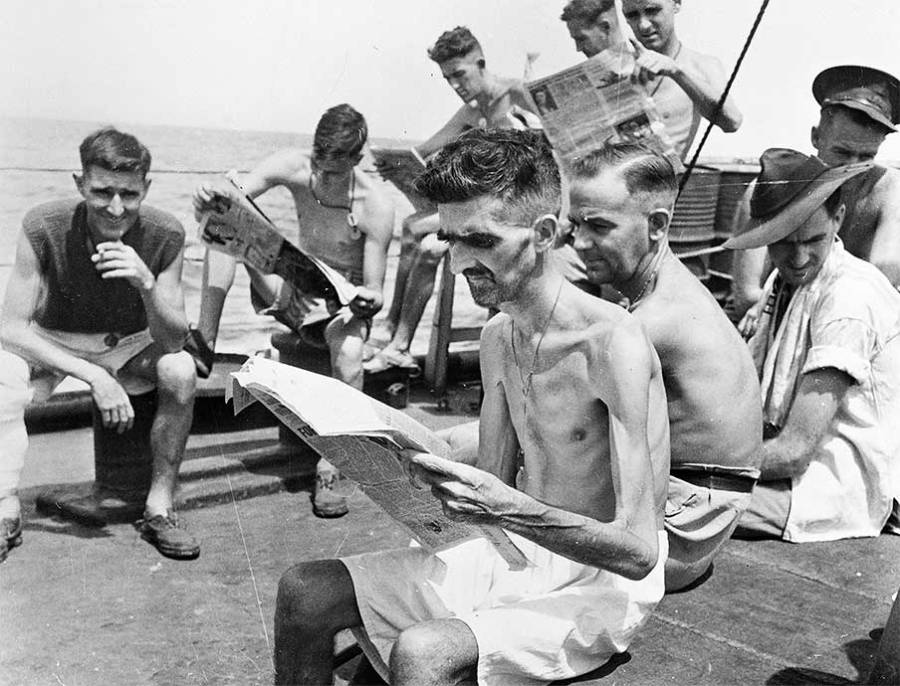 Shown to the right is a photo of men, with Private Leo Ayres in the foreground, newly liberated from the Japanese camps who were reading the newspapers about the war having just ended.