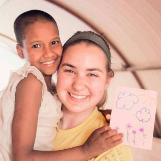Emily Goette holds the little girl in a Nepali orphanage as the girl holds up Draper's letter.