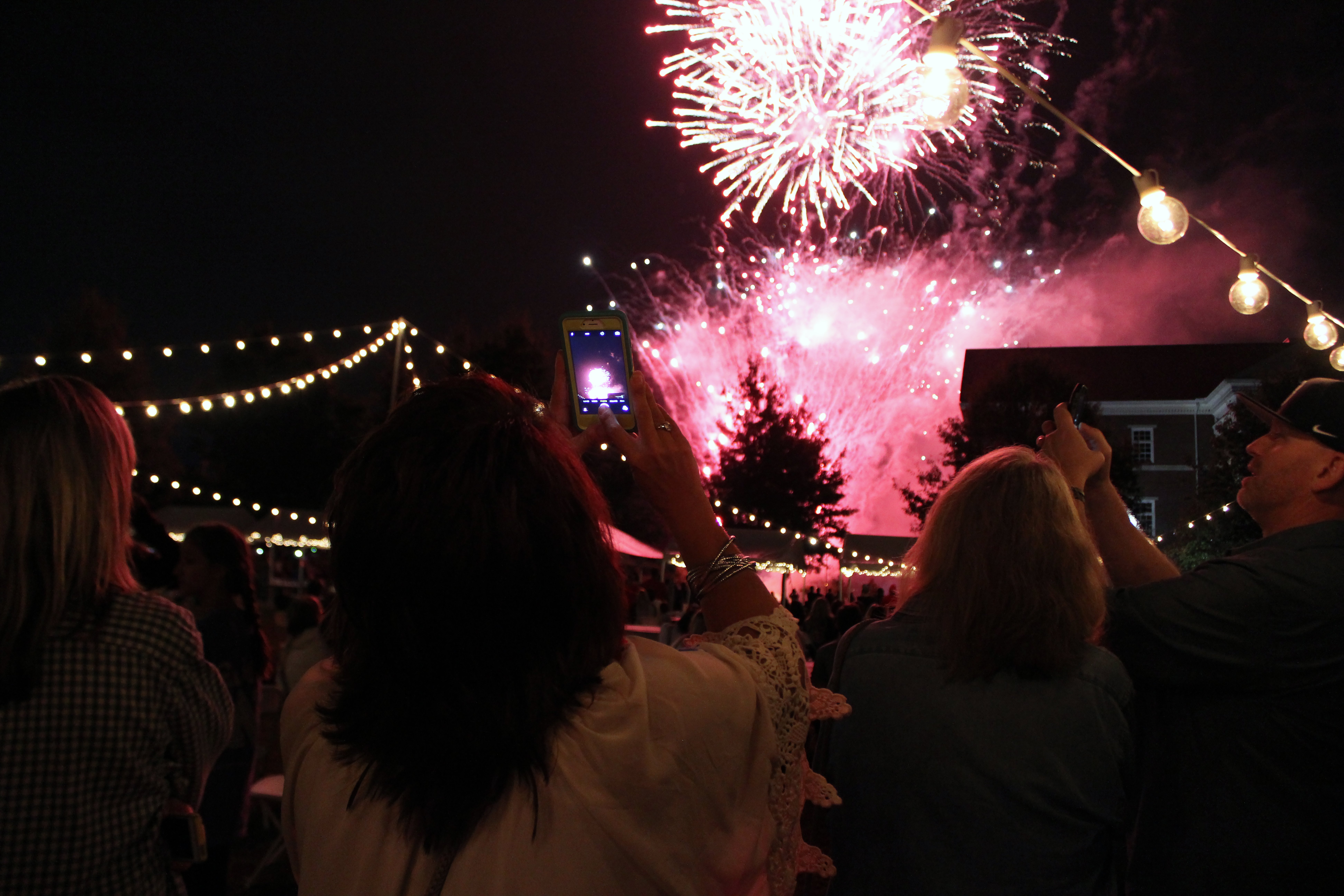 Parents, siblings, and students take snapshots of the dazzling fireworks during the Union Night event on Family Weekend.