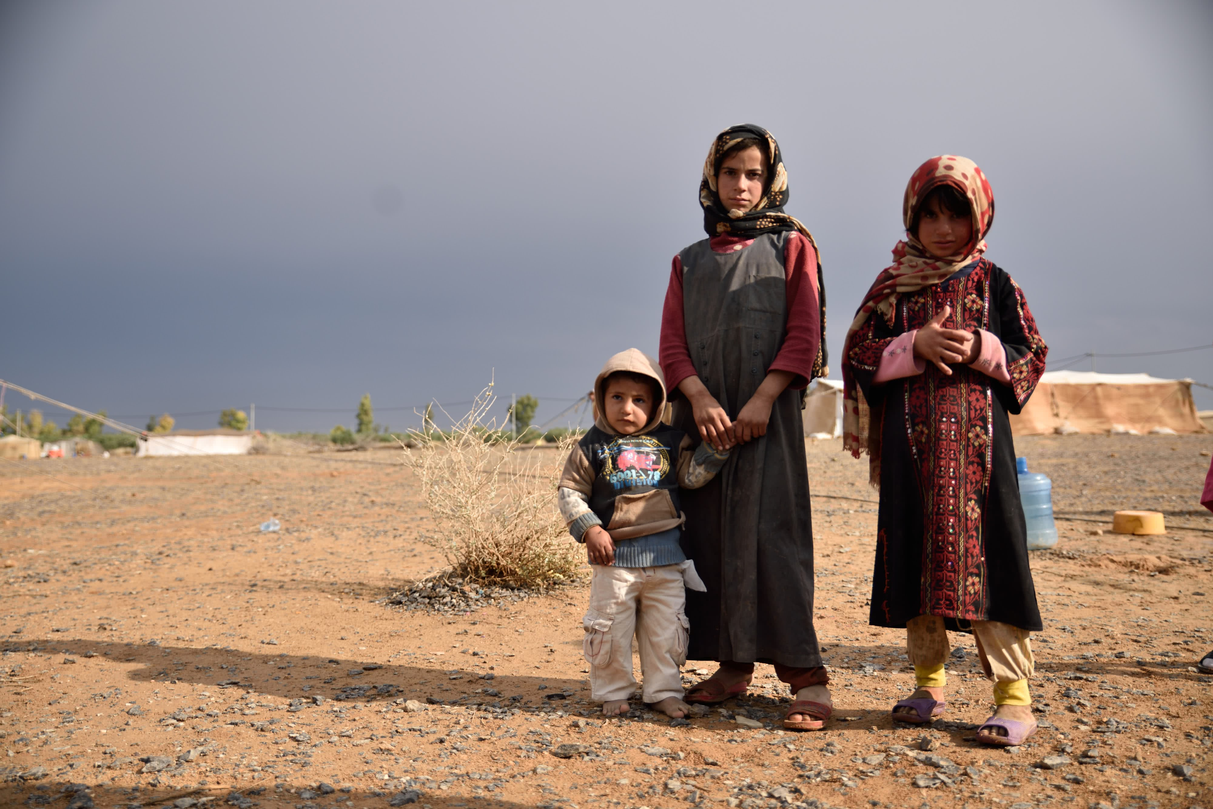 3 young Syrian girls standing in the middle of no where looking at the camera with sadness