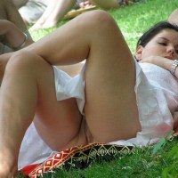 Lying down in a park in a short dress and accidentally showing her shaved pussy