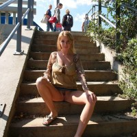Sitting on the steps in a short skirt showing her bottomless pussy