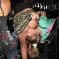 Exposing her ass and pussy in a short skirt inside a bar and getting it licked by her friend