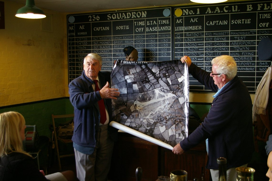 John Brock MBE displays German aerial photograph of RAF Carew Cheriton taken on 29th Sept. 1940 prior bombing raid that killed wounded airmen in the airbase hospital.