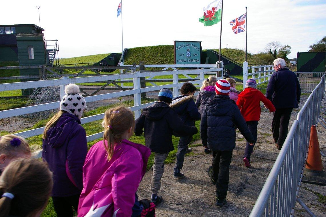 Museum volunteer march Gelli Aur Golden Grove pupils and their teachers around the Carew Cheriton site.