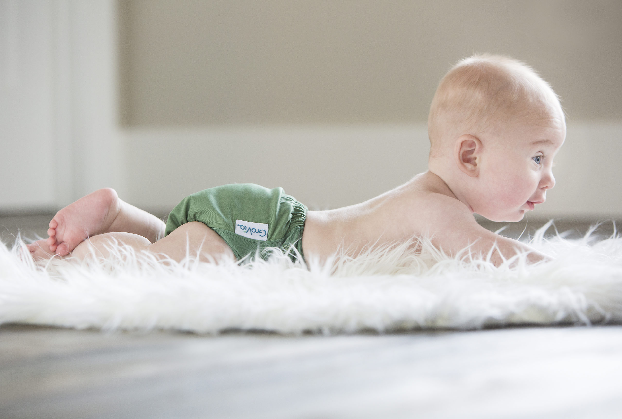 young baby in a grovia basil laying on its tummy on a fluffy white rug