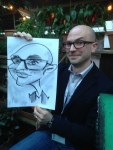 Man with glasses holding caricature by Allan Cavanagh