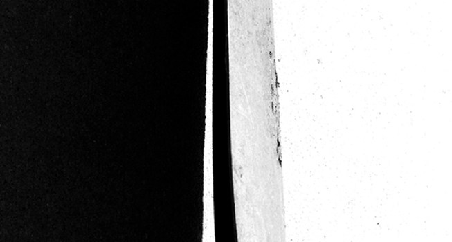 A shovel casts a broad shadow on concrete.