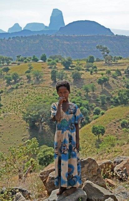 Una niña posa para nosotros con el Monte Aza de fondo