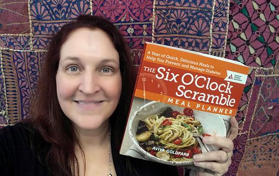 Carma holding her copy of The Six O'Clock Scramble by Aviva Goldfarb