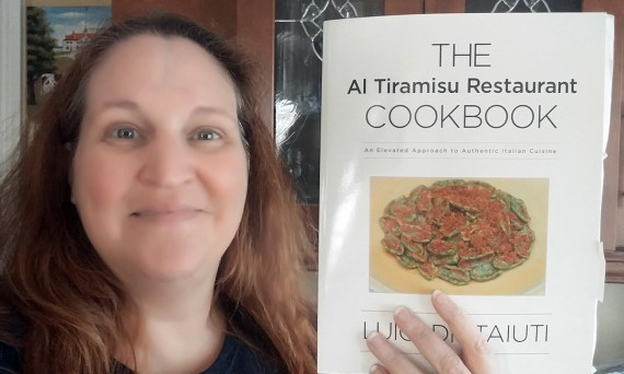 Carma Spence holding a copy of The Al Tiramisu Restaurant Cookbook