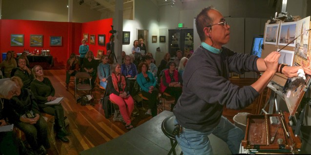 A captive audience watches Calvin as he demonstrates a seascape oil painting.