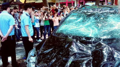 People take pictures of a Japanese car damaged during a Chinese protest last month
