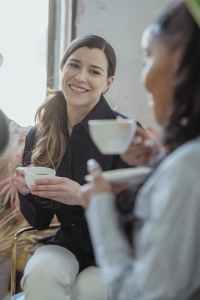 positive diverse friends talking and having cup of coffee - café y la salud