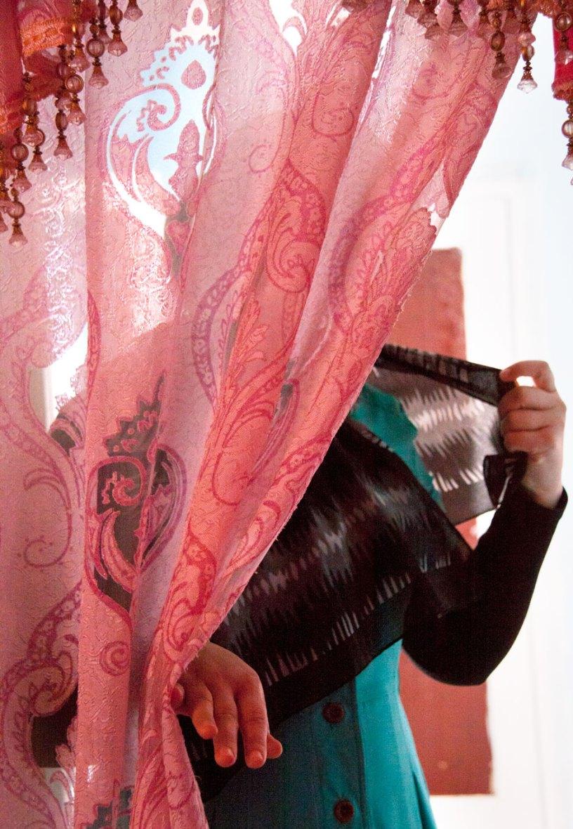 Afghanische Frau hinter einem Vorhang