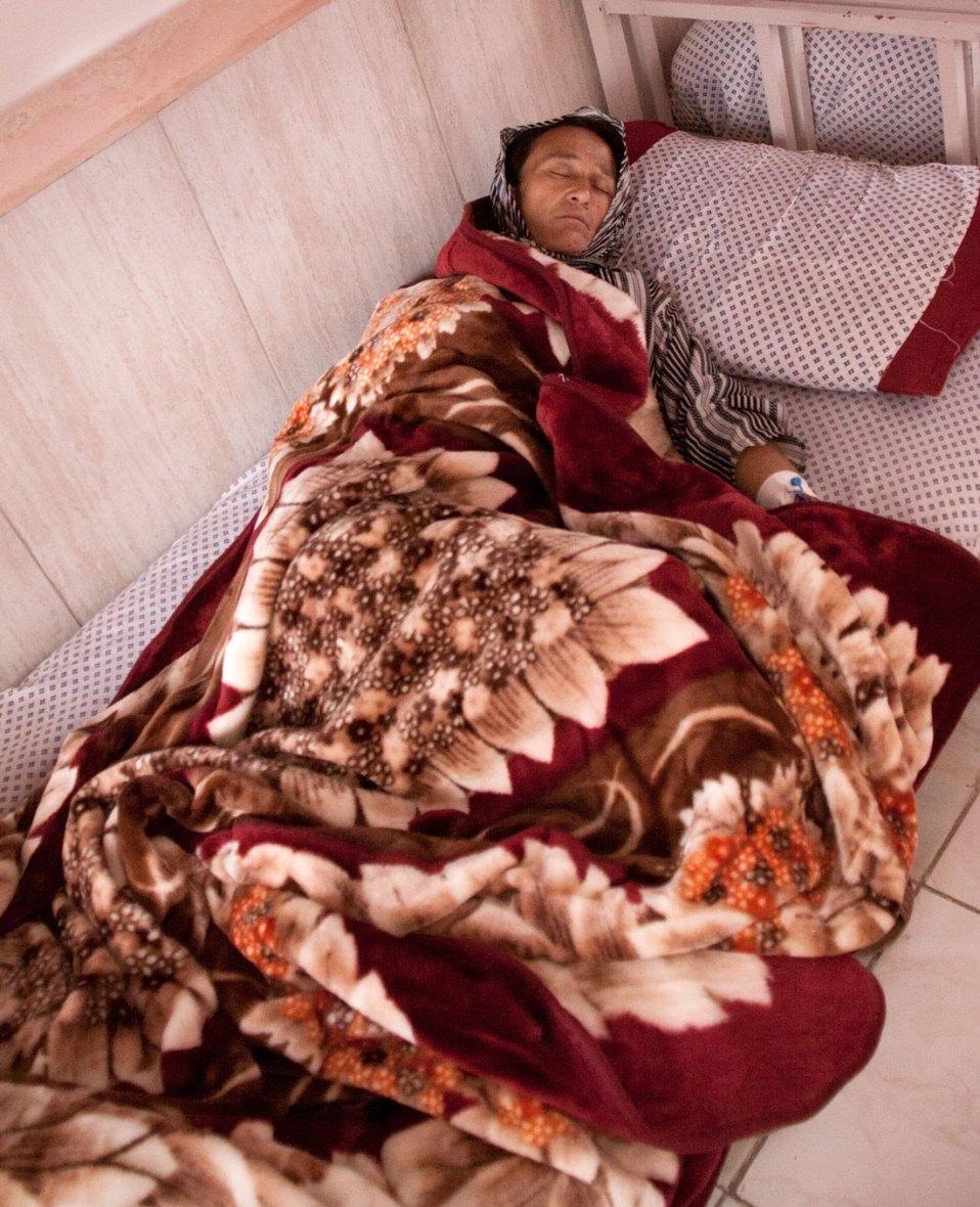 Afghanische Frau unter einer Blumendecke schläft im Bett