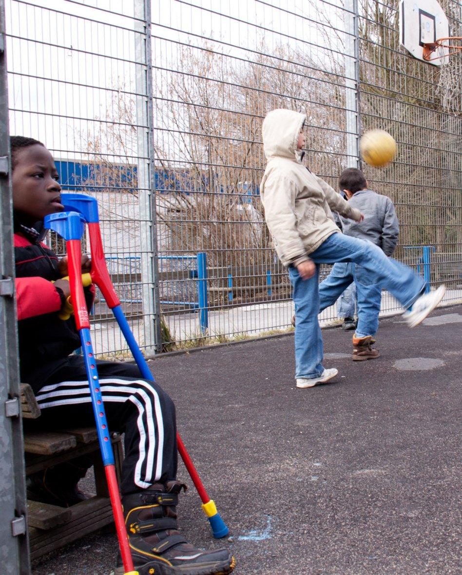 Kind mit Krücken und Kind mit Fußball