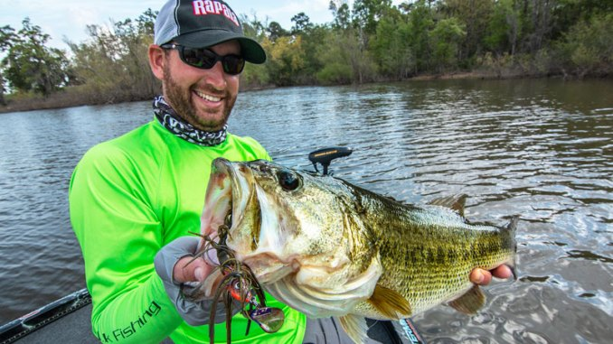 Ott DeFoe, the 2019 Bassmaster Classic Champion and Major League Fishing pro angler, holds up a big bass caught on a Terminator Shuddering Bait.