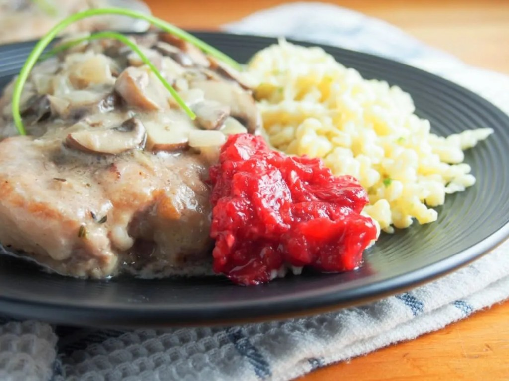 Jaegerschnitzel with cranberry-raspberry sauce - the German classic 'hunter's cutlet' with a mushroom-wine sauce is serve with a delicious, easy cranberry-raspberry sauce. Perfect comfort food.