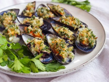 baked mussels on plate with parsley garnish to side