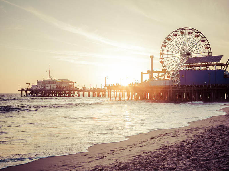 Santa Monica Pier retro sunset picture with Santa Monica Beach and the Pacific Ocean. Photo has a vintage nostalgic tone. Santa Monica Pier is a landmark that has an amusement park with a ferris wheel, roller coaster, restaurants, and other attractions. Image Copyright © Paul Velgos All Rights Reserved.