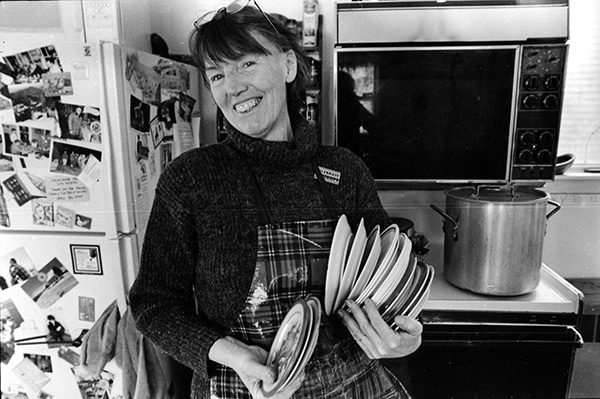 Ruth Ives with a stack of bowls in the kitchen