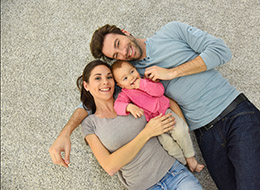 family laying on a clean carpet together