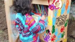 enfant qui déposent un livre dans un Croque-Livres