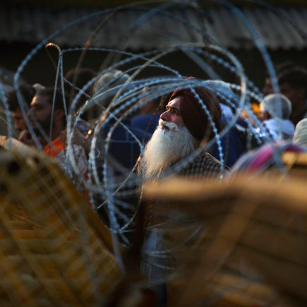 Indian farmer looking through barbed wire, put up by police at the Delhi-Haryana border.
