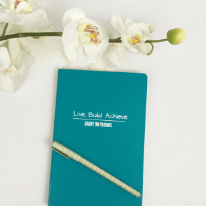 Live Build Achieve Journal with pen and flowers
