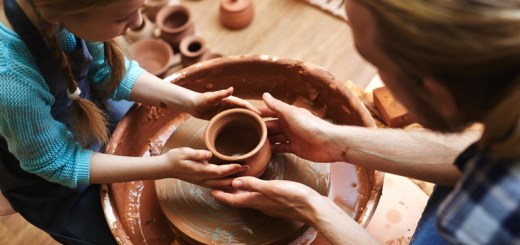 Top view of man and his daughter making jugs in pottery-wheel