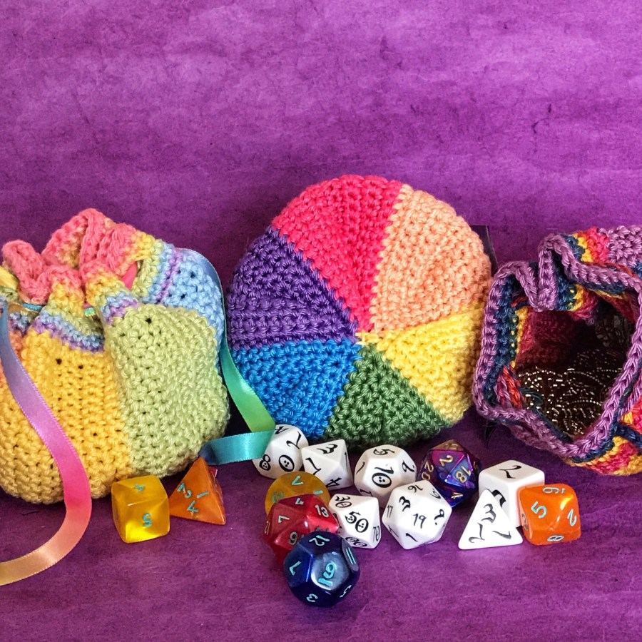 Three dice pouches in a spectrum of colors