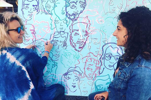 Photo of artist Davia King making a portrait