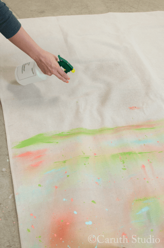 Spraying water on drop cloth for watercolor tablecloth