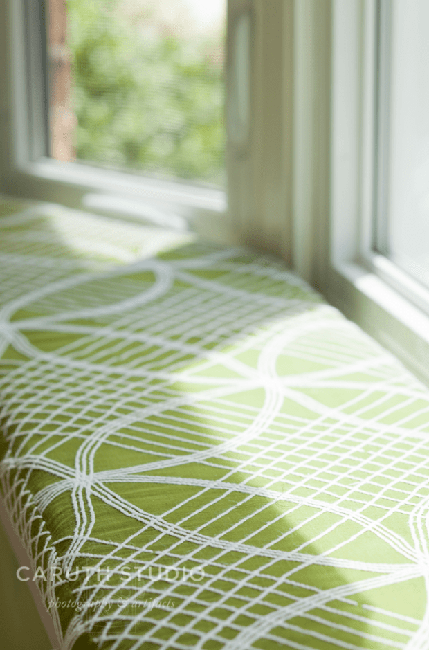 green window seat with white line details