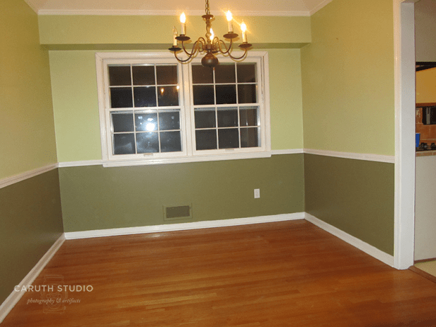 Dining room before makeover with two shades of green with dividing white chair rail and small brass chandelier