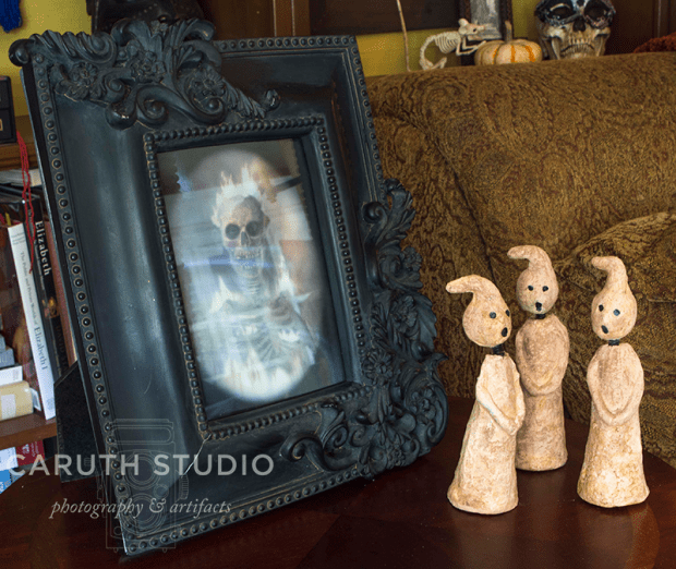 framed ghostly skeleton image with three singing ghost figurines to the right
