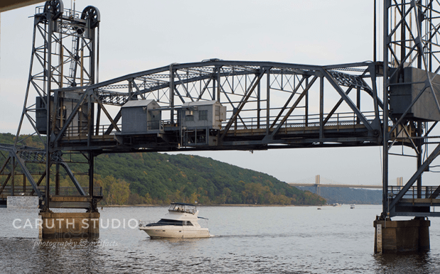 lift bridge moving up, allowing a yacht to float underneath