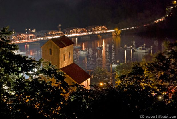 looking down at stillwater minnesota at night - trees, the top of the tall grain elevator-restaurant and the river with the old lift bridge