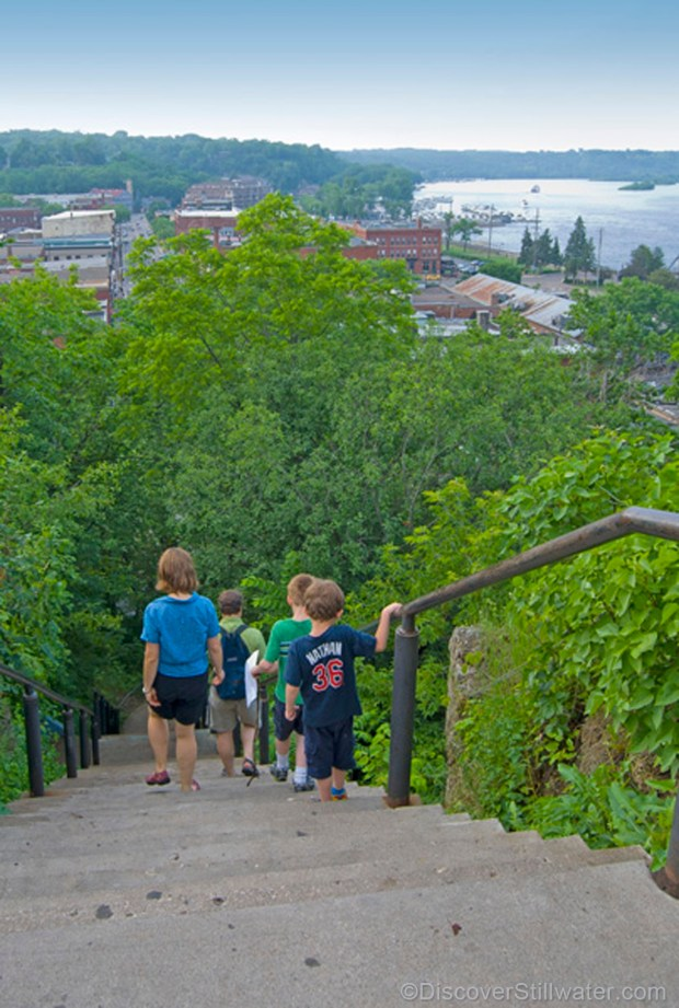 children descending the main stairs towards historic Stillwater Minnesota with the town and the river in the background