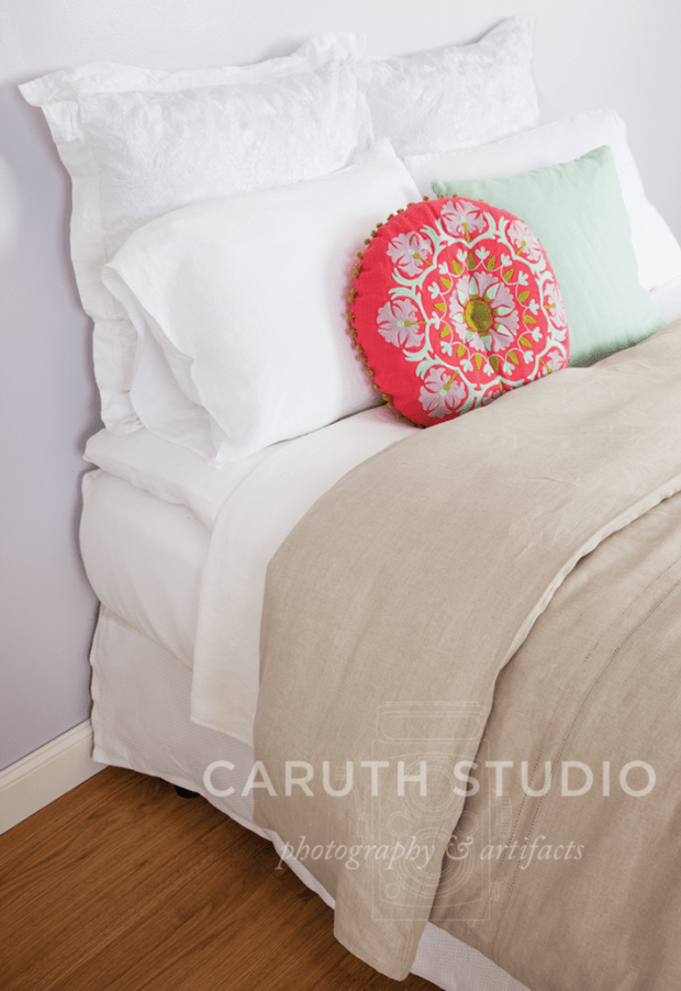 kaki duvet on top of white sheets and a circle pink pillow and mint square decorative pillow rest against white pillows