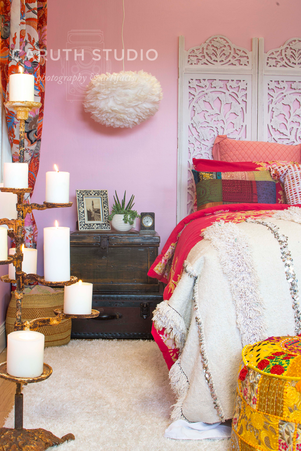 boho bed, nightstand of trunks and golden candle stand