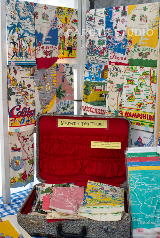 assortment of vintage table and kitchen napkins with a red suitcase display