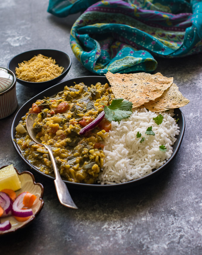 Drumstick leaves dal, rice, sev and sald on a board.