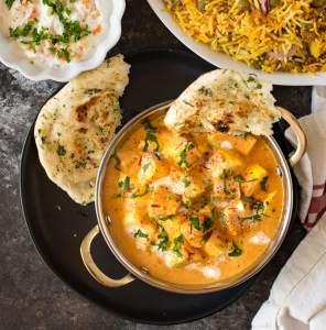 Shahi paneer curry served with vegetable raita , naan and rice.