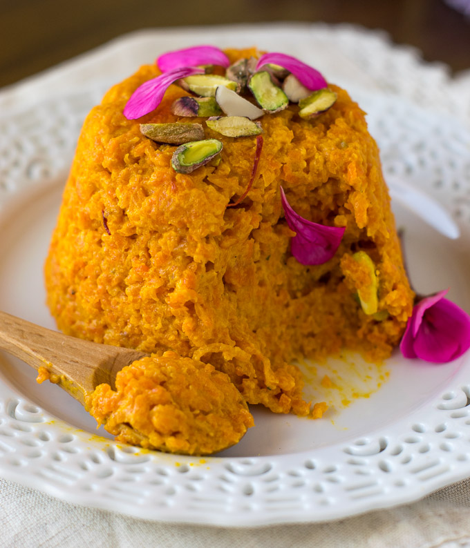Gajar halwa garnish with flowers and eaten with a spoon